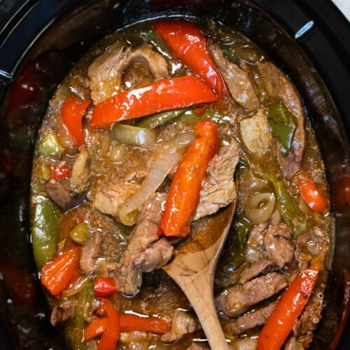 pepper steak in slow cooker with wooden spoon in it.